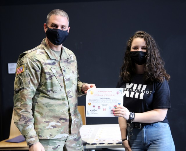 Col. Michael R. Kaloostian, 2nd Theater Signal Brigade Commander, presents Emily Benjamin with a Certificate of Excellence for her contributions to the Wiesbaden High School's Air Force Association United States CyberPatriot program. Members of the program earned first and second place honors during AFA US CyberPatriot Challenge in the Gold Tier, At-Large Open Division in the State Round. (U.S. Army photo by Candy Knight)