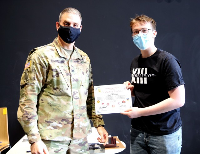 Col. Michael R. Kaloostian, 2nd Theater Signal Brigade Commander, presents Skylar Broussard with a Certificate of Excellence for his contributions to the Wiesbaden High School's Air Force Association United States CyberPatriot program. Members of the program earned first and second place honors during AFA US CyberPatriot Challenge in the Gold Tier, At-Large Open Division in the State Round. (U.S. Army photo by Candy Knight)