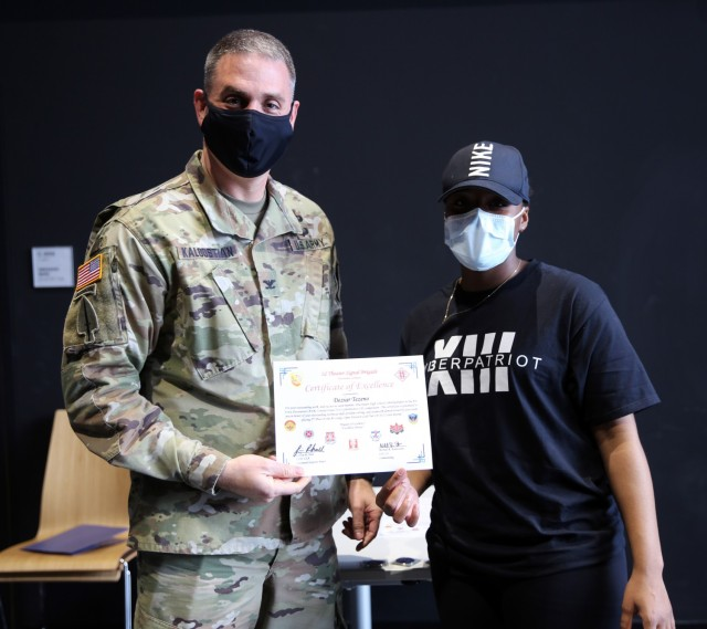 Col. Michael R. Kaloostian, 2nd Theater Signal Brigade Commander, presents Deziar Tezeno with a Certificate of Excellence for her contributions to the Wiesbaden High School's Air Force Association United States CyberPatriot program. Members of the program earned first and second place honors during AFA US CyberPatriot Challenge in the Gold Tier, At-Large Open Division in the State Round. (U.S. Army photo by Candy Knight)