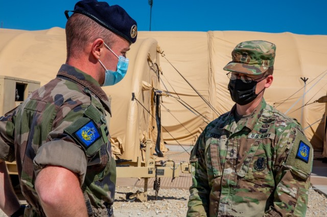 French Army Capt. Arnaud Raedersdorf and Army Master Sgt. Brandon Bybee of the French Rapid Reaction Corps, French III Division take a break from the day's briefings during Warfighter 21-4 March 29, 2021 at Fort Hood, Texas. U.K. and French Soldiers worked together during the exercise to certify their respective corps and build multinational interoperability. U.S. Army photo by Sgt. Evan Ruchotzke).