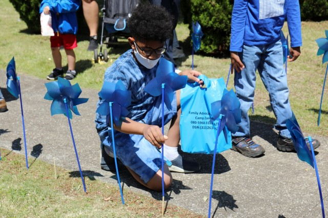 Noah Mills, 9, plants a pinwheel during the U.S. Army Garrison Japan Army Community Service pinwheel planting commemoration of National Child Abuse Prevention Month at the Sagamihara Family Housing Area Library, SFHA, Japan, April 23.