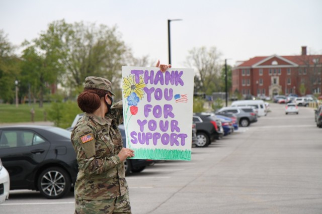 Sgt. Tuu Valaau, human resources noncommissioned officer, 1st Theater Sustainment Command, looks over her shoulder at children as they arrive at Kingsolver Elementary School, Fort Knox, Kentucky, April 23, 2021. The Soldiers created posters and cheered on the families of the Fort Knox community in observance of the Month of the Military Child. The month of April is designated as Month of the Military Child to let children know that their resiliency and ability to change and adapt is appreciated.  (U.S. Army photo by Staff Sgt. Nahjier Williams, 1st TSC PAO)