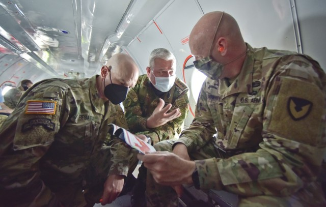 Maj. Gen.Elder Giraldo, chief of operations for the Columbian Army, center, briefs Brig. Gen. Douglas Lowrey, commander of U.S. Army Security Assistance Command, during a quick huddle inside a Colombian aircraft flying over Colombia, 5 April 2021. Lt. Col. Andrew Pesature, left, Army Chief of Missions at U.S. Embassy, provides translation services. Lowrey and members of his staff visited several sites to see the impact of U.S. security assistance and foreign military sales, in support of the Colombian military in defending their country from counter-narcotic and internal terrorist threats. (U.S. Army photo by Richard Bumgardner)