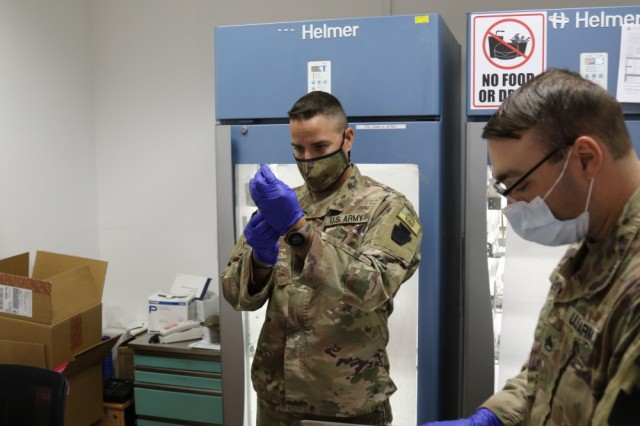 Sgt. Austin Peters, left, and Staff Sgt. Dave Yanetti, both medical specialists with the 28th Expeditionary Combat Aviation Brigade, prepare syringes with the COVID-19 vaccine at a medical clinic in the 28th ECAB's area of operations in the Middle East in March 2021.