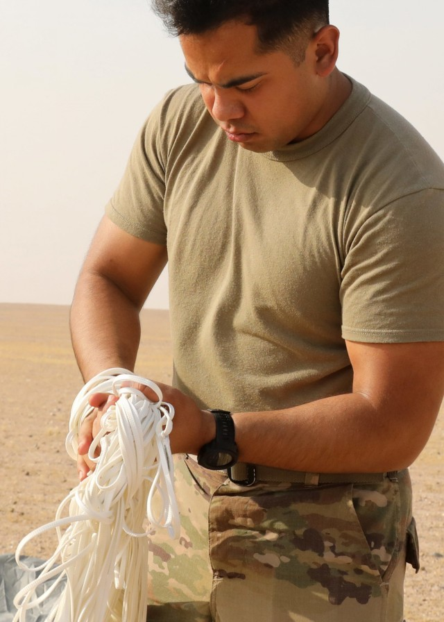 Rigger Spc. Andres Sanchez with the Fort Bragg, North Carolina, based 151st Quartermaster Company, deployed to the U.S. Central Command area of responsibility in support 1st Theater Sustainment Command, collects the rigging lines from one of the four parachutes that each successfully carried bundles within 75 meters of the target at the Camp Buehring, Kuwait, drop zone April 22, 2021 using the Joint Precision Air Delivery System, or JPADS. Sanchez said he appreciated the chance to participate in the real-world exercise. (U.S. Army photo by Staff Sgt. Neil W. McCabe)