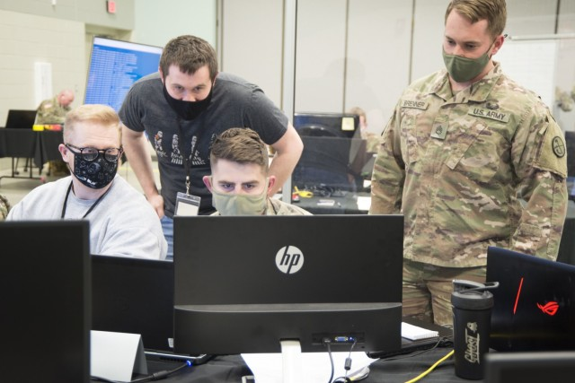 U.S. Army Staff Sgt. Paul Coffy (center, seated) views the status of the virtual exercise environment as two West Virginia University students and U.S. Army Staff Sgt. Adam Brenner (right) observe. For Locked Shields 2021, the West Virginia National Guard, Illinois National Guard, and West Virginia University students participated together out of the Morgantown National Guard Readiness Center as a joint Blue Team with Poland the week of April 12th. (Photo by U.S. Air Force Staff Sgt. Mallory Coleman)