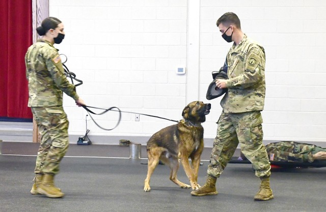 Spc. Monica Wilson (left) holds the leash of military working dog, Ben, as they demonstrate a take down on Pvt. Christopher LaBelle.