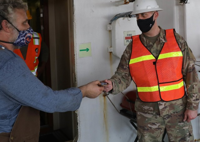 """Deputy Commanding General of the 1st Theater Sustainment Command Brig. Gen. Justin M. Swanson presents his commander's coin to Capt. Peter Matesic aboard Matesic's container ship Sagamore during Swanson's April 24, 2021 tour of ammo off-load-on-load operations at Kuwait's Port Shuaiba. After receiving the coin from Swanson, Matesic said of the general's visit: """"It's an awesome experience, it shows the importance of the mission and the importance of what we are doing here."""" (U.S. Army photo by Staff Sgt. Neil W. McCabe)"""