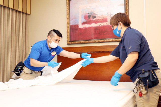 Javar Sarabie, left, housekeeper, and Masayo Hoshino, housekeeping leader, prepare a room for new guests at Camp Zama Army Lodging, Camp Zama, Japan, April 28.