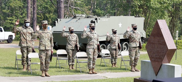 Soldiers raise their right hand as they recite the Oath of the Noncommissioned Officer administered at the Bayne-Jones Army Community Hospital Noncommissioned Officer Induction Ceremony held April 21.