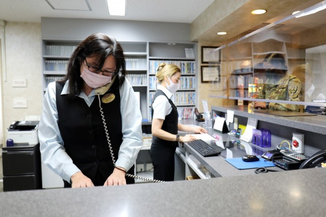 Yuko Otsuka, left, assistant manager of Camp Zama Army Lodging, and Shealy Tae Kyong, front desk supervisor, work at the facility's front desk, Camp Zama, Japan, April 28.