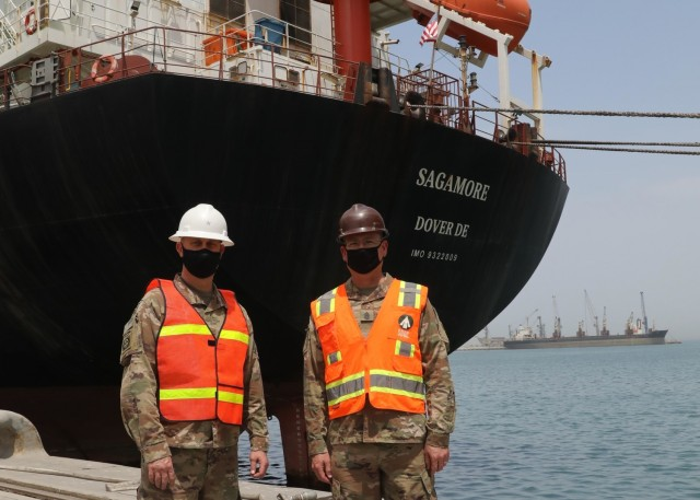 Deputy Commanding General of 1st Theater Sustainment Command Brig. Gen. Justin M. Swanson stands with his senior enlisted advisor Command Sgt. Maj. Keith A. Gwin in front of the container ship Sagamore during their April 24, 2021 tour of ammunition off-load-on-load operations by 1st TSC Soldiers deployed with the 595th Transportation Brigade (SDDC) and the 1185th Deployment and Distribution Support Battalion, assigned to Kuwait's Port Shuaiba. (U.S. Army photo by Staff Sgt. Neil W. McCabe)