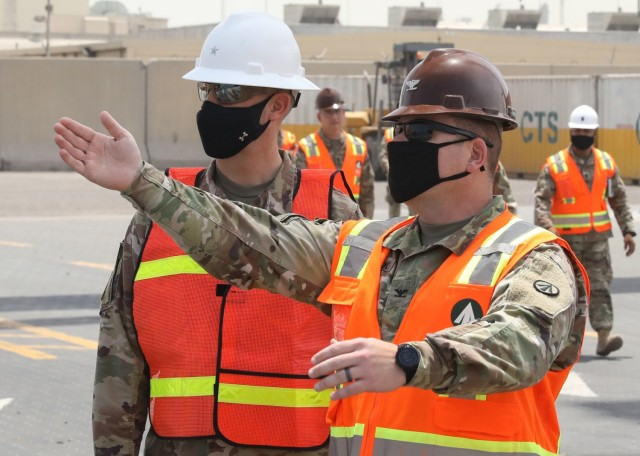 Col. Michael Ludwick, commander of 595th Transportation Brigade (SDDC), gestures while he describes port operations to Brig. Gen. Justin M. Swanson, the deputy commanding general of the 1st Theater Sustainment Command, while on Swanson's April 24, 2021 tour of Kuwait's Port Shuaiba. The 595th TB (SDDC) integrates and synchronizes surface deployment and distribution capabilities to project readiness and sustain the warfighter throughout the U.S. Central Command area of operations. (U.S. Army photo by Staff Sgt. Neil W. McCabe)