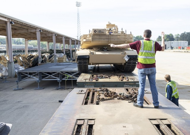 Landon Magouryk and Wayne Hubbard (right) guide an M1A1 Abrams tank onto a railcar using the RAIL turn pad platform configuration during a demonstration at Anniston Army Depot.