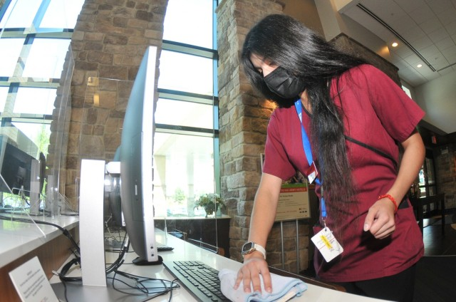 Fort Lee Holiday Inn Express employee Yagani Santiago tidies up the computer area in the hotel lobby April 28. The Army Lodging facility has more than 30 job openings that will be promoted at the Fort Lee Hiring Expo set for 9 a.m. - 2 p.m. May 13 at the Lee Club. (U.S. Army Photo by T. Anthony Bell)