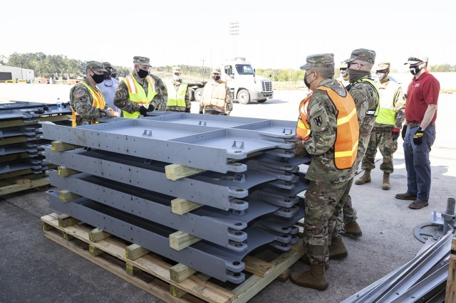Soldiers from the 757th Expeditionary Rail Center are guided by Justin Strickler (far right), division chief at the Geotechnical and Structures Laboratory at the U.S. Army Engineer Research and Development Center, as they prepare to configure a pod platform.