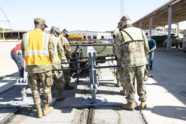 Soldiers from the 757th Expeditionary Rail Center configure the rear off-load platform for the RAIL system during a demonstration at Anniston Army Depot.