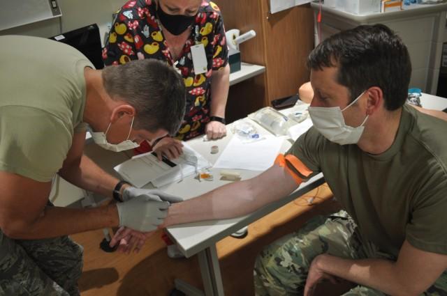 Martin Army Community Hospital 3rd-year resident Capt. Weston Pratt practiced inserting a peripheral IV in fellow 3rd-year resident Capt. Benjamin Kight under the watchful eye of Strong Team Registered Nurse Cynthia Avera.