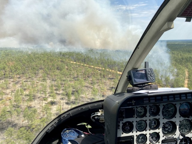 A smoke plume is seen from above following a controlled burn, April 23 on Fort Stewart, Georgia. The contracted helicopter is used to drop small balls of incendiary substances to burn hardwood plants in the Fort Stewart-Hunter Army Airfield training area, April 23 on Fort Stewart.
