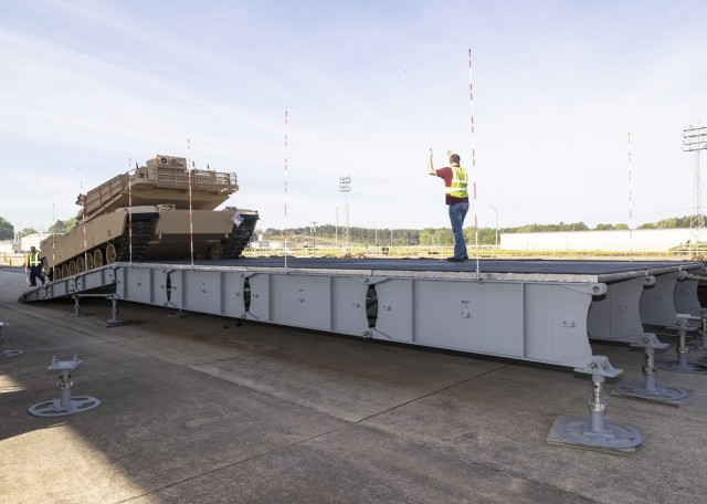 Barron Dulaney, a Defense Logistics Agency Distribution Anniston employee, is guided by Landon Magouryk, a DLA Distribution employee, as he drives an M1A1 Abrams tank onto a platform using a rear off-load platform configuration.