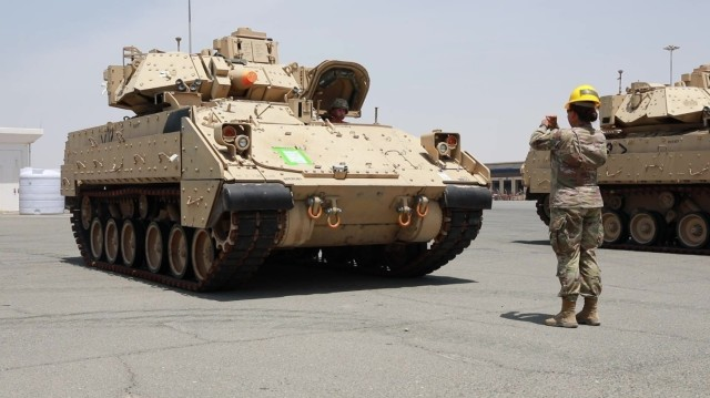Capt. Shayna Taylor, officer in charge of the port support element, 1st Battalion, 35th Armored Regiment, 2nd Brigade Combat Team, 1st Armored Division, ground guides the driver of an M2/A2 Bradley Fighting Vehicle to the proper staging area as part of the logistics exercise, LOGEX 21, at  the industrial port at Yanbu, Kingdom of Saudi Arabia April 20, 2021. LOGEX 21 demonstrates the 1st Theater Sustainment Command's readiness and ability to provide responsive support to U.S. and partner nation forces from anywhere in the U.S. Central Command theater, exercising the Trans-Arabian Network.  (U.S. Army photo by Capt. Elizabeth Rogers)