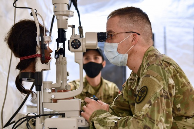 Lt. Col. Keith Schmidt, Chief of Optometry at the Madigan Army Medical Center, conducts a test of the Ophthalmic Slit Lamp while Staff Sgt. Tara Laramee, a Test Officer with the U.S. Army Medical Test and Evaluation Activity takes notes.