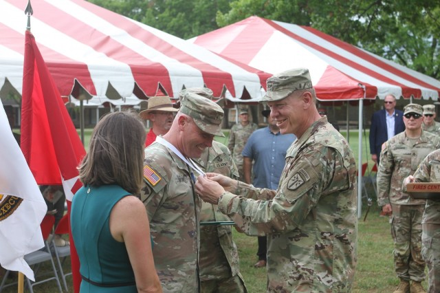Maj. Gen. Ken Kamper, Fires Center of Excellence and Fort Sill commanding general, enjoys the moment as he drapes the Legion of Merit on Brig. Gen. Phil Brooks while talking with Brooks' wife, Lori, left.