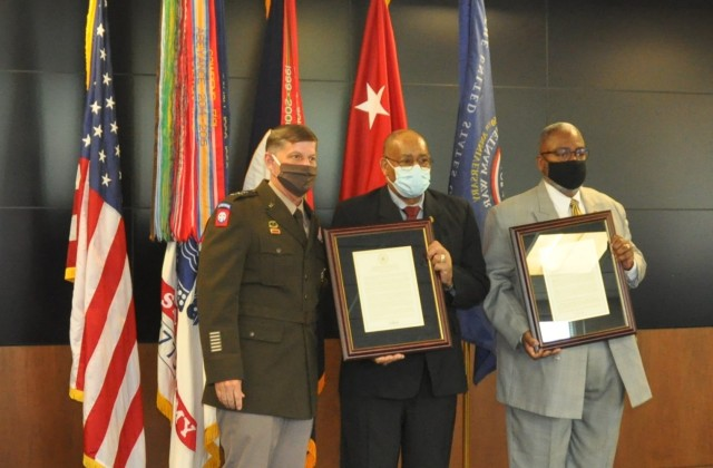 Vietnam veterans Burnie Coats, center, and David Lewis receive plaques commemorating the recognition of the 50th anniversary of the Vietnam War during a Vietnam Veterans Commemoration program hosted by Army Materiel Command at Redstone Arsenal, Alabama. The plaques were presented by AMC Deputy Commander Lt. Gen. Donnie Walker.