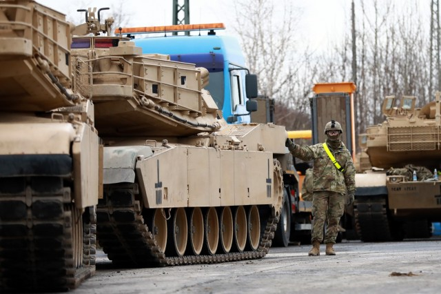A U. S. Army Soldier assigned to the 1st Armored Brigade Combat Team, 1st Cavalry Division, guides M1 Abrams Main Battle Tanks at Parsburg, Germany, in preparation for transfer to Poland, Mar. 13, 2021.