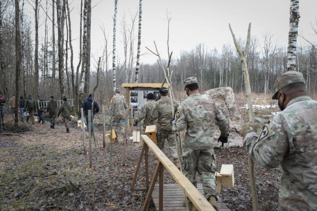Troopers assigned to 2nd Battalion, 8th Cavalry Regiment, follow military cadets from the General Povilas Plechavicius cadet lyceum into the forest in Kaunas, Lithuania on March 13, 2021, to hang bird houses they made. The joint efforts show community members cadets and Troopers are good stewards of the environment. (U.S. Army photo by Sgt. Alexandra Shea)