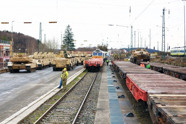 The scene at the railhead as U.S. Army Soldiers assigned to the 1st Armored Brigade Combat Team, 1st Cavalry Division, load armored vehicles in preparation for transfer to Poland, at Parburg, Germany, Mar. 13, 2021.