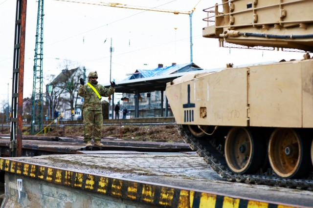 A U. S. Army Soldier assigned to the 1st Armored Brigade Combat Team, 1st Cavalry Division, guides an M1 Abrams Main Battle Tank onto a railcar in preparation for transfer to Poland, at Parsburg, Germany, Mar. 13, 2021