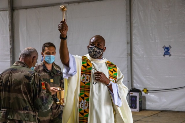 Capt. Raymond Akirewe, a chaplain with 1st Cavalry Division, uses an aspergillum to bless assembled French soldiers during a French-language Easter mass at Fort Hood, Texas, April 4, 2021. The implement dates to ancient times and is used to disperse holy water on the congregation at the start of major liturgies. (U.S. Army photo by Sgt. Evan Ruchotzke)