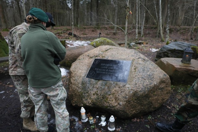 Capt. Spenser Swafford, Fire Support Officer assigned to 2nd Battalion, 8th Cavalry Regiment, and Lithuanian Liaison Officer Lt. Emile Mazeikaite, Griffin Brigade, read a stone marker placed in the forest Lithuanian freedom fighters occupied for over ten years as they gained their independence from the Soviet Union. Swafford, along with his fellow volunteers, visited the historical site on March 13, 2021, after helping to hang bird houses with military cadets from the General Povilas Plechavicius cadet lyceum. (U.S. Army photo by Sgt. Alexandra Shea)