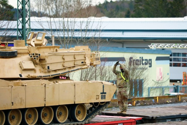 A U. S. Army Soldier assigned to the 1st Armored Brigade Combat Team, 1st Cavalry Division, guides an M1 Abrams Main Battle Tank onto a railcar in preparation for transfer to Poland, at Parsburg, Germany, Mar. 13, 2021.