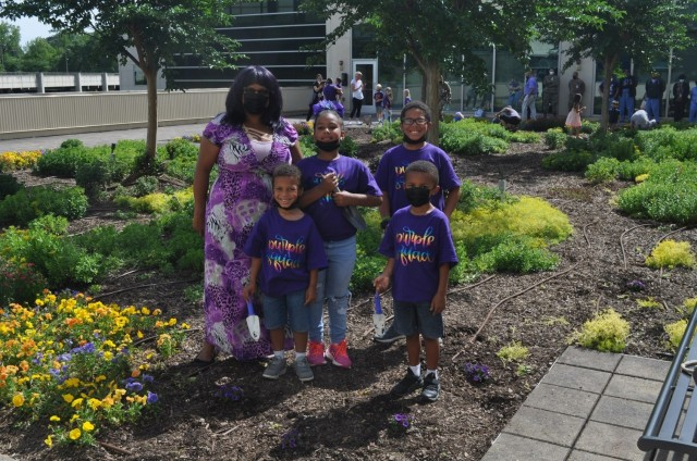 The Olszak family pose after planting purple flowers as part of Martin Army Community Hospital's Month of the Military Child celebration.