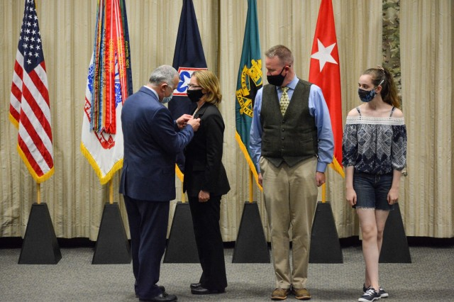 John Hall, Headquarters Department of the Army G4 principal deputy (left), presents Sydney Smith, Army Logistics University president, with the senior executive service pin Friday, April 30, 2021, at the Army Logistics University Green Auditorium. Smith's husband, Tim, and daughter, Molly, watch the presentation. Members of the SES serve in the key positions just below the top presidential appointees and alongside general officers.