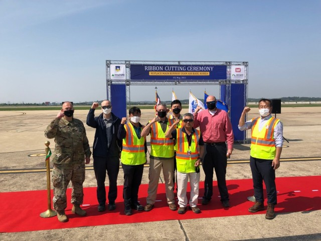 Col. Christopher Crary (Left), U.S. Army Corps of Engineers (USACE), Far East District (FED) commander and members of the FED Project Delivery Team attended a ribbon cutting ceremony for the replacement of the main runway on Osan Air Base, Republic of Korea, May 3, 2021.