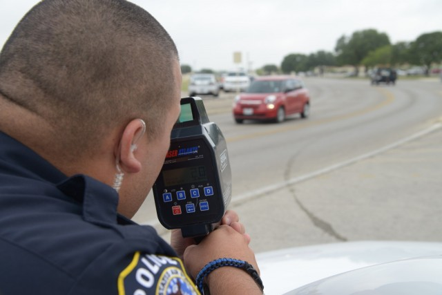Officer Marcelo Aguillon, 902nd Security Forces uses his speed laser equipment to record vehicle speeds July 9 at Joint Base San Antonio-Randolph. (U.S. Air Force photo by Joel Martinez)