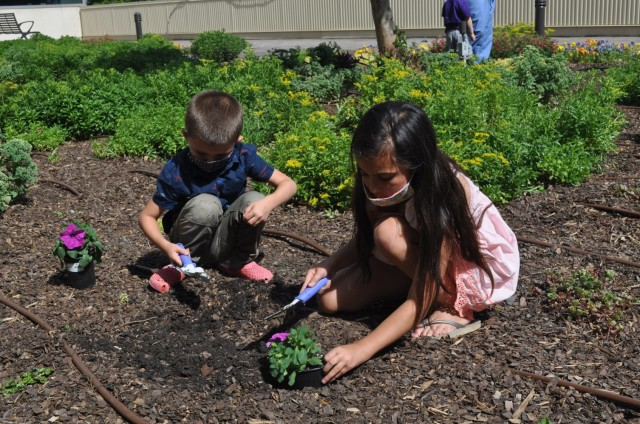 Nine-year-old Brooklyn McDaniel along with her younger brother Cameron plant purple flowers as part of Martin Army Community Hospital's Month of the Military Child celebration.