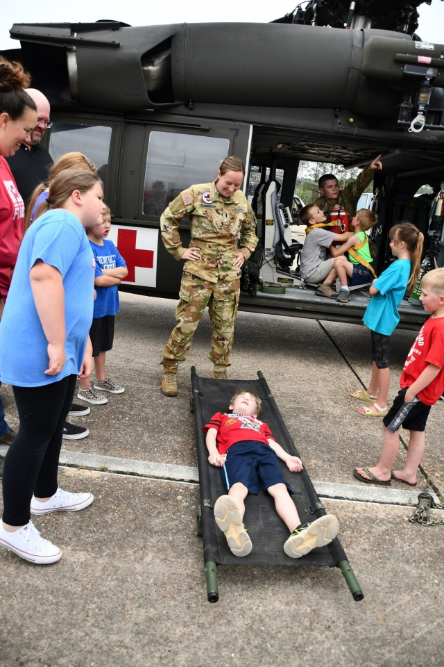 Above: 1st Lt. Katie Rummery, Cajun Dustoff pilot, looks on as Calvin Walker gets on the litter to try it out.