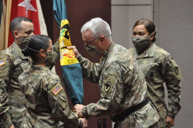 Maj. Gen. Paul H. Pardew, commanding general of U.S. Army Contracting Command (right) passes the colors of the organization to Command Sgt. Maj. Julie Saorrono (left) in a change of responsibility ceremony conducted at the Bob Jones Auditorium on Redstone Arsenal May 3. Saorrono becomes the first MOS 51C to  serve as ACC's senior enlisted advisor to the commanding general.