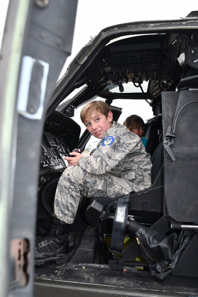 Cadet Airman Wesley Walker, 12, gets a feel for the controls in the cockpit of a UH-60 Blackhawk.