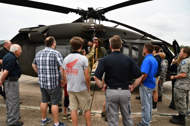 The tour continues outside as participants watch 1st Lt. Katie Rummery, pilot, and Spc. Chase Roberts, crew chief, — members of Cajun Dustoff — as they attach a hoist to the medical helicopter.