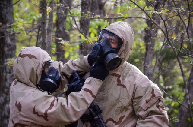 Competitors complete a buddy check to ensure their chemical protective clothing is properly secured and ready for follow-on operations at Training Area 125.