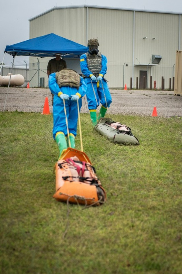 A team drags simulated casualties at one of six stations testing CBRN knowledge and soldiering skills April 29 outside the Chemical Defense Training Facility.
