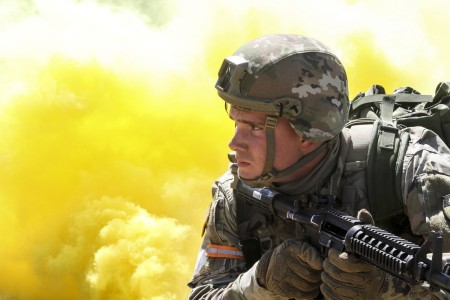 Army Spc. Caleb Romero, a California National Guardsman, scans his sector as smoke billows behind him during the mystery event of the California Guard's Best Warrior Competition at Camp Roberts, Calif., March 31, 2021