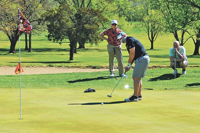 Burt Clark putts on Hole 9 as his teammates, from left, Cara Kendall and Gregg Daily look on Friday during the Commanding General's Scramble at Piney Valley Golf Course.