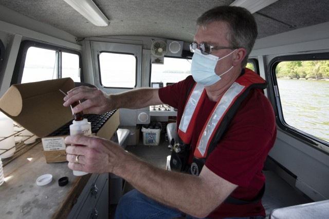 Mark Campbell, hydrologist in the U.S. Army Corps of Engineers Nashville District's Water Management Section, puts a preservative into a chlorophyl sampling on a survey boat in J. Percy Priest Lake in Nashville Tennessee April 27, 2021. (USACE Photo by Leon Roberts)