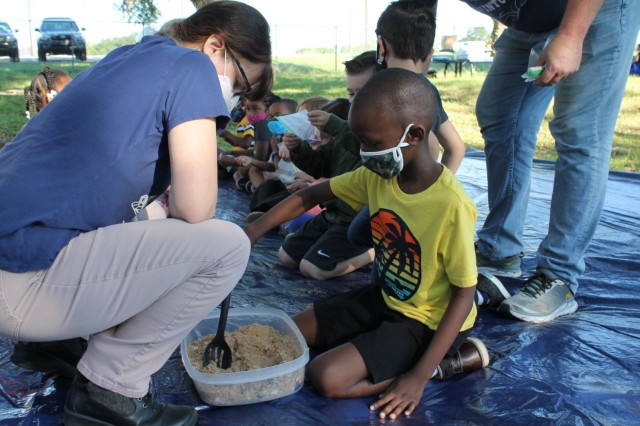 Kelly Norwood, a geologist, helps with a little hands-on learning at the Geology station during the U.S. Army Environmental Command Nature Walk held for about 140 kindergarteners from the Fort Sam Houston Elementary School.